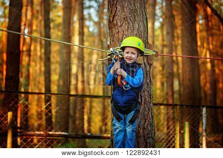 Little Happy Child Boy In Adventure Park In Safety Equipment In Summer Day.