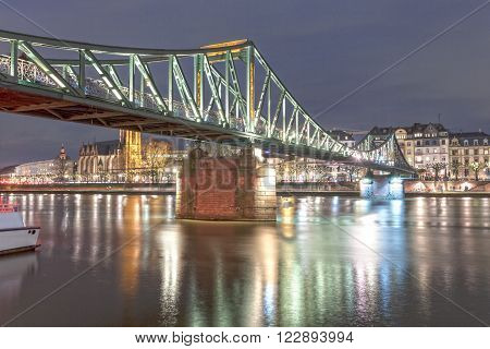 Old iron bridge over the Main river in Frankfurt Main illuminated at night. Hesse Germany