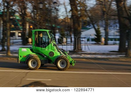 Moscow, Russia - December 8, 2016: Little green tractor on cleaning the Gorky Park
