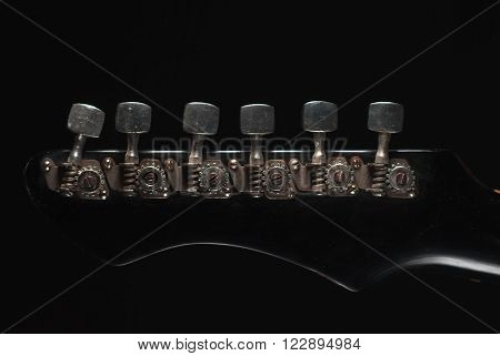the mechanism of a tension of strings on the fingerboard of an old vintage electric guitar