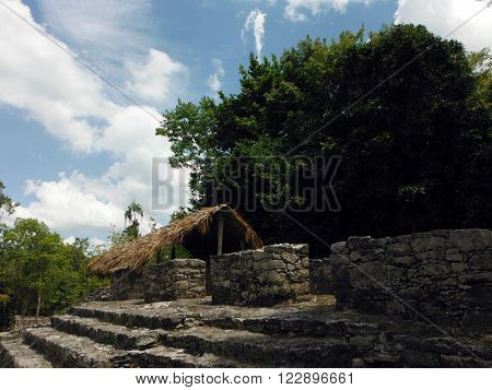 A thatched hut protecting ancient art at the Coba Mayan archeological site in Yucatan Peninsula Mexico.