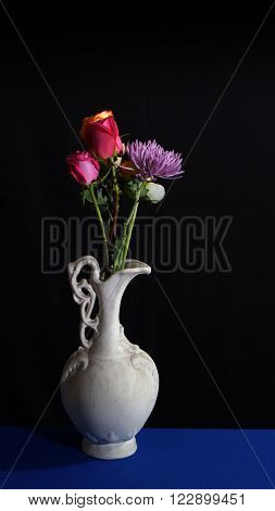 Flowers in old white ceramic vase on dark background in vertical format