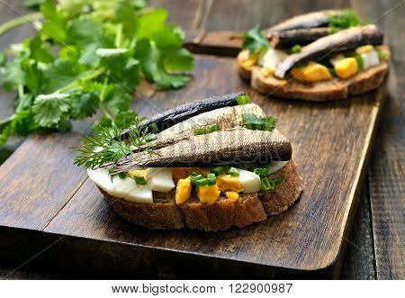 Sandwich with sprats egg and green onion on wooden cutting board