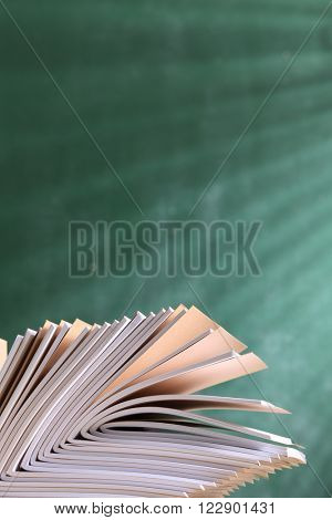 workbook on top of table in front of blackboard