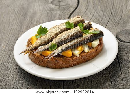 Sandwich with sprats and egg on wooden table close up
