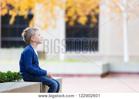 beautiful thinking boy sitting in the park enjoying autumn weather