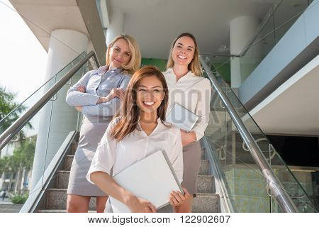 Cheerful attractive business ladies standing on staircase