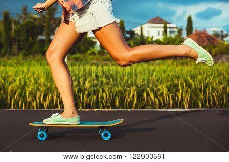 Girl skateboarder legs skateboarding at sunset rice fields