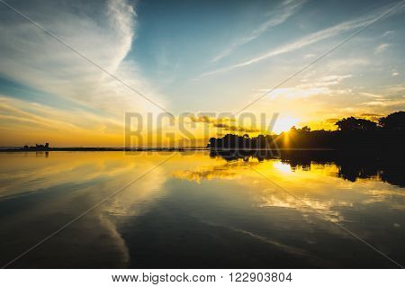 Sun rise from the trees and reflect together with clouds and sky in the water surface. Striking sunset above the ocean bay with bright clouds and sky.