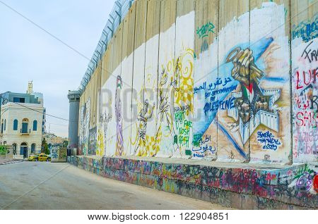 BETHLEHEM PALESTINE - FEBRUARY 18 2016: The separation wall becomes the place for street murals that shows the author's point of view on the realities of the life on February 18 in Bethlehem.