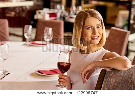 She looks incredible. Pretty young woman is sitting at the restaurant with glass of wine.