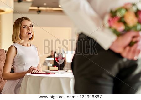 Delightful evening. Young beautiful woman is looking impressed by man with flowers in the restaurant.
