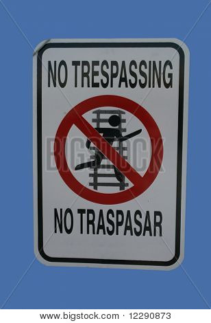 Bilingual no trepassing on railway sign in English and Spanish