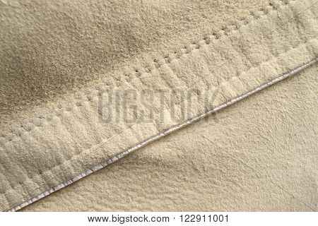 Macro shot of a diagonal stitch on beige suede