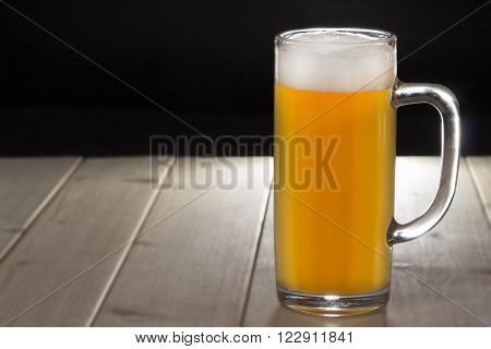 Mug of unfiltered beer on the wooden table. Backlight. Black background ideal for adding the background scene.
