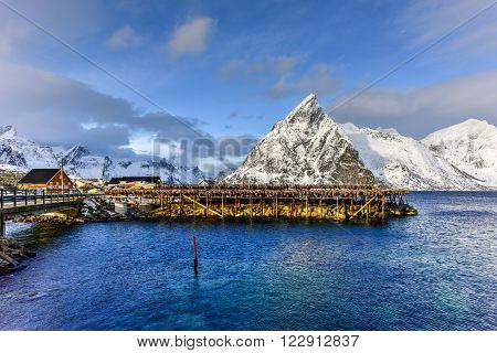 Fishing hut (rorbu) in the Hamnoy and Lilandstinden mountain peak in winter in Reine, Lofoten Islands, Norway.