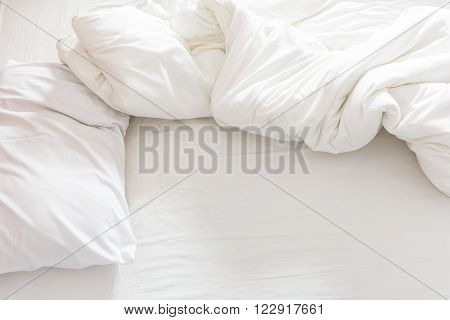 Top view of an unmade bed with a pillow a bed sheet and a blanket after waking up in the morning.