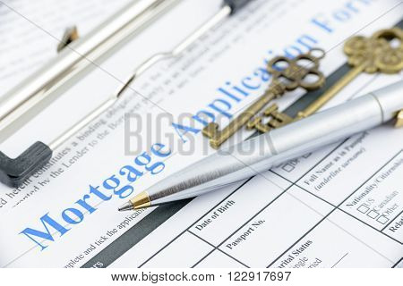Blue ballpoint pen and two vintage brass keys on a mortgage application form, preparation for filling a form on a clipboard.
