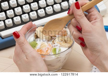 Bowl of muesli with fresh banana, kiwi and tangerine. Female hand holding wooden spoon. Typewriter in the background.