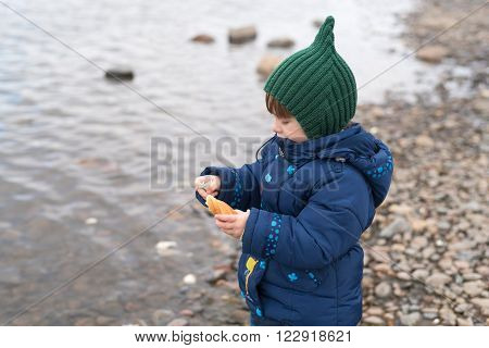 Girl with a piece of bread on a river bank