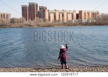 Girl dropping stones into river on a cityscape background