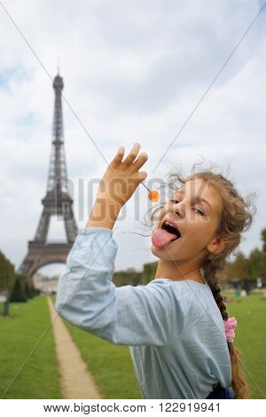 Portrait of a little girl with a lollipop in Paris