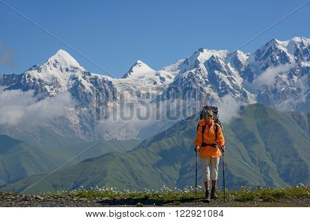 Tourist against high mountains background. Woman is situated on alpine meadow.