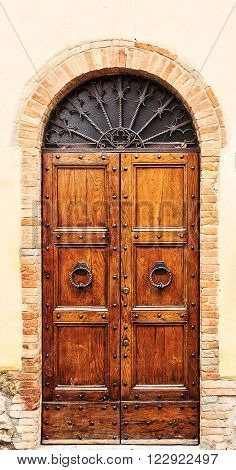 Brown wood old door in the centre of San Gimignano Tuscany Italy.