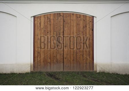 Big wooden barn gate. Monumental farm door, two timber leaf, closed brown gateway with planks and nails. Exterior country situation. Rural entry architecture element. Village foundation background.