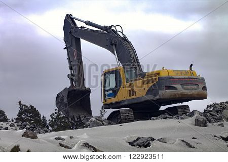 Crawler excavator is working on the top of the granite rock in dull winter day.
