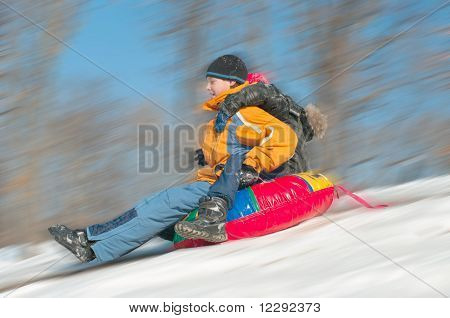 Young Boys Sledding Downhill Together