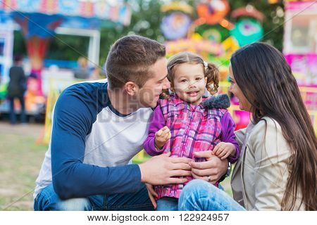 Father, mother and daughter having fun in amusement park, fun fair ** Note: Visible grain at 100%, best at smaller sizes
