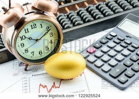 A golden egg with a clock a calculator and an abacus on business and financial summary reports. A long term sustainable growth investment concept.