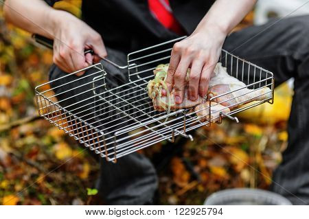 Raw chicken shashlik on the grill and male hands