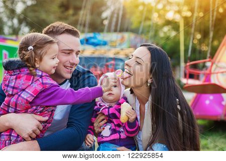 Young family with little girls enjoying time at fun fair, baby eating roll, mother eating popsicle, amusement park