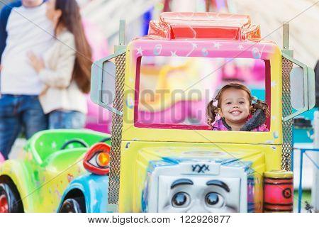 Little girl enjoying  a truck ride at fun fair, amusement park