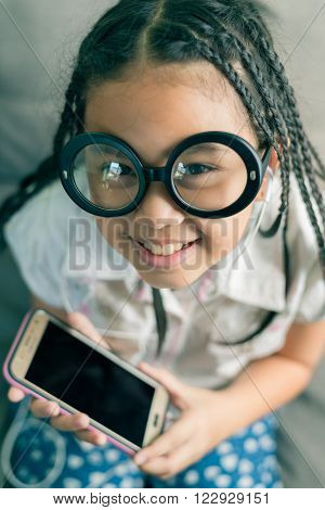 Cute little girl wearing glasses dreadlocks hair style playing with computer at home laying on sofa ** Note: Shallow depth of field
