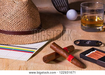 Siesta - cigar straw hatScotch whiskey and golf driver on a wooden table