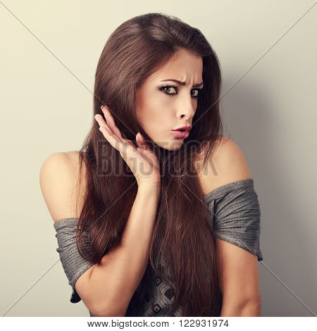 Refused Grumpy Young Brunette Woman With Hand Hear Face And Surprising Eyes. Toned Closeup Portrait