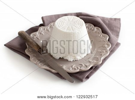 Italian ricotta cheese with knife on napkin isolated on white