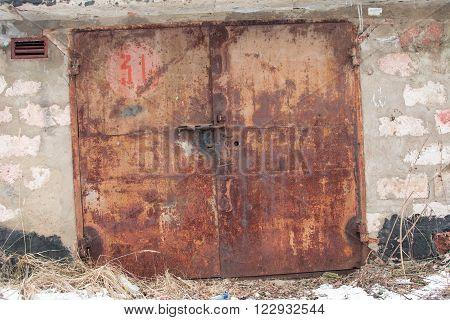 metal red door with lock. brick background