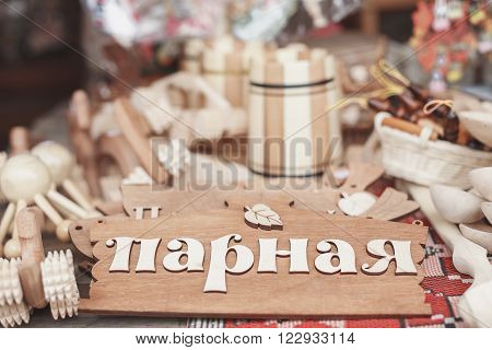 wooden plaque with the inscription on the door of the steam room of the bathhouse. Around wooden objects, cups, glasses, are made of wood. All the items on the table