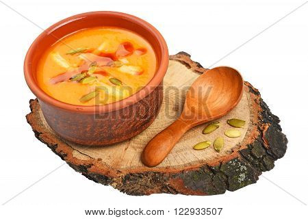 Small ceramic bowl of pumpkin cream soup wooden spoon slice of bread and seeds on wood cut isolated on white background high angle view