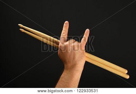 Man Hand With Drumsticks And Devil Horns Over Black