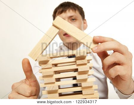 Inventor.  Businessman building tower of wooden blocks