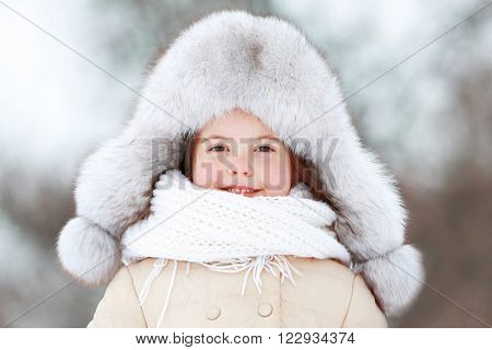 Little girl with fur hat in snowy park outdoor, close up