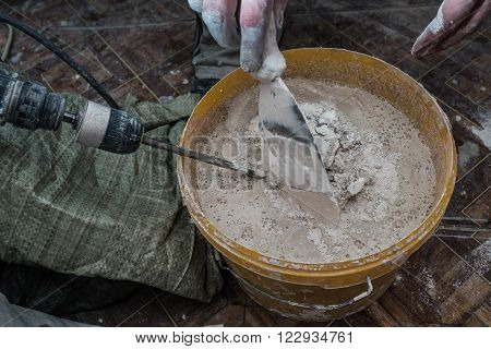 Construction worker man stirs the mixture in the bucket construction for alignment and putty walls of the apartment with the help of a powerful drill.