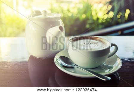 Cup of coffee with hot tea pot on wooden and blur background Vintage tone