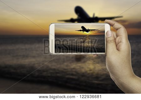 Hand of women with smart phone shooting photograph on blurred airplane and beach sunset in twilight