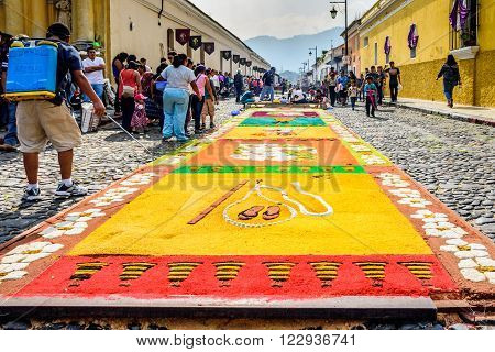 Antigua Guatemala - March 20 2016: Spectators admire handmade dyed sawdust carpet as local man waters it outside Hermano Pedro church & hospital for Palm Sunday procession in colonial town with most famous Holy Week celebrations in Latin America.